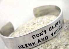 """A narrow, shiny aluminum bracelet hand-stamped by me with """"Don't blink. Blink…"""