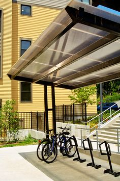 Covered outdoor bike parking with the Slope Bike Shelter and Varsity Bike Dock bike racks from Park A Bike. #BikeRacks #BikeShelter