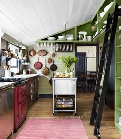 I WANT this kitchen. It is near perfect: The olive green wall, the library ladder for reaching high up utensils, the window over the sink, the rolling island and the collection of pans decorating the wall. I seriously don't think I would change a thing.
