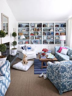 """Bookshelf design trick: """"Provide visual interest by arranging some books horizontally,"""" says @Eddie Ross. """"You can also place accessories atop the stacks."""" Coating the built-in unit's interior with a pale blue adds depth."""