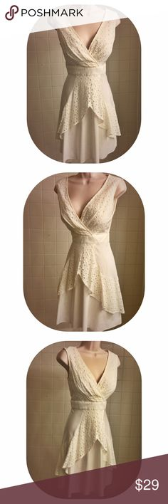 """Sleeveless Ivory Eyelet Overlay Max & Cleo Dress This pretty & elegant cream colored sleeveless v-neck dress from Max & Cleo is perfect for a special occasion, day or night! The faux wrap up top of the dress is comprised of Eyelet, adding a delicate feminine touch to the dress. The dress is cinched at the waist w/ a band of fabric, creating a flattering silhouette. Under the waistline, the A-line skirt falls. The front of the skirt is detailed with a draped layer detailed in eyelet. 35"""" in…"""
