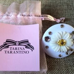"""Tarina Tarantino White Daisy Cake Ring  6.5 Tarina Tarantino """"Classic"""" White Daisy Cake Mod Ring Size 6.5 NWT  The TARINA TARANTINO """"Classic"""" White Daisy Cake Mod Ring will add fun sparkle to your cocktail party outfit.  A wide silver-plated base supports a round cake-like disc made of white Lucite, decorated with Swarovski clear white crystals and a sweet little daisy flower in the center. Gold crystals glitter from the middle of the daisy for even more bling.  2 inches in diameter. Size…"""