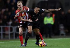 Sebastian Larsson of Sunderland (L) fouls Nathaniel Clyne of Liverpool (R) during the Premier League match between Sunderland and Liverpool at Stadium of Light on January 2, 2017 in Sunderland, England.