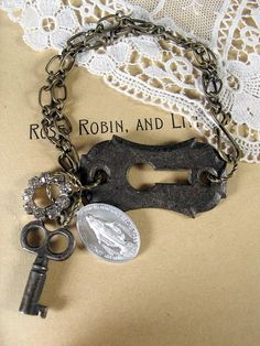 Handmade Repurposed Assemblage Bracelet. This sweet bracelet starts with a black antique escutcheon. Dangling from the end of the doubled chain