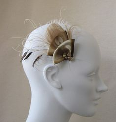 """Beautiful taupe peacock feather with ivory swirled peacock sword and hand curled fronds. Lovely spray of three bronze eyelash feathers. Champagne ivory and bronze edged silk ribbon. Decorated with vintage pearls, net covered citrine vintage jewel. Backed with black leather for stability and metal hair clip.  Feathers lay beautifully on head and is 3.5"""" wide by 'BaroqueAndRoll' on Etsy."""