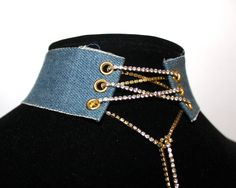 """This 1.5"""" denim choker with a rhinestone chain laced up is surely a statement piece. You can choose between denim with a silver tone rhinestone chain/eyelets, or a gold tone rhinestone chain/eyelets.It also features a spring ring clasp and adjustable chain in the back, so there is no hassle of lacing up for every wear.PRODUCT CAREAs with all chokers, you should handle with care. Let it sit on your lower neck, and make sure you give yourself room to move and be comfo..."""