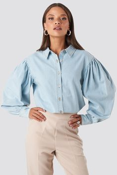 This denim shirt features a classic collar, a button closure on the front, puff sleeves and a double button cuff. Shirt Blouses, Shirts, Denim Trends, Urban Chic, Blouse Online, Minimal Fashion, Ruffle Top, Mannequin, Denim Shirt