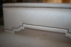 "Upholstered Cornice, SHAPE: Step Curve Step. COLOR: Off White FABRIC: Dupioni Silk. TRIM: Antique Brass Nailheads 1/23"" Diameter. Made by Maribel Claribel Interiors."