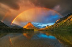 After a rainy night in Glacier National Park, Montana (USA), storms give rise to a rainbow.