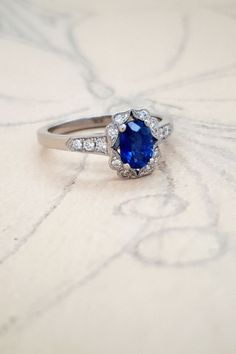 This sapphire and diamond engagement ring is set with an oval sapphire weighing 0.89 carat. A halo of eight round diamonds encircles the sapphire. A further three diamonds cascade down each side of the platinum band. #LondonVictorianRing #BlueSapphire #SapphireRing #SapphireEngagementRing #HaloEngagementRing #VintageRingDesign