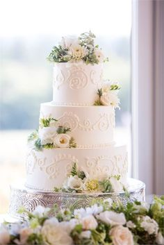 A pretty, traditional, three tiered wedding cake decorated with ivory and green flowers and covered in elegantly detailed icing.