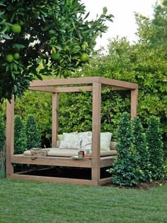 This canopy-style daybed is situated on the edge of this tree-filled yard, so it's the perfect place to relax and still take in the action. Design by Jamie Durie
