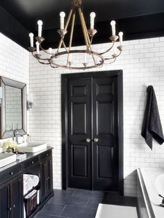 While color trends come and go, black and white remains a classic combination. As in fashion, this high-contrast duo creates drama in any space. Here, designer Brian Patrick Flynn transformed this contractor-grade bathroom into an elegant, classic space with white subway tile walls, black porcelain tile floors and an aged iron chandelier.