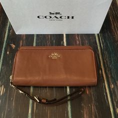 COACH Wallet NWT Brand new beauty! brown soft leather authentic Coach Wallet with gold hardware/zipper. Double zipper compartments with tons of internal storage space. Detachable wrist Leash. Use as either a wristlet or a wallet.                       ‼️‼️ NO Trades‼️‼️             offers appreciated thru the offer button.              〽️ercari always has listing at a lower price ! Coach Bags Wallets