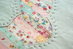 This is a good idea for using very small scraps of fabric. I would probably choose another shape to put the strips under, but this technique would be nice in a quilt.