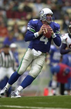 Trent Dilfer of the Seattle Seahawks goes back for a pass against the Denver Broncos at Husky Stadium in Seattle Washington The Seahawks won 3421...