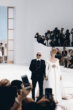 Karl Lagerfeld takes his bow with a pregnant Ashleigh Good as the Chanel bride at Chanel Haute Couture AW14.