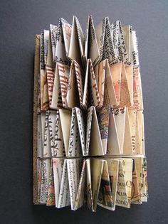 From book to book sculpture by Helen Malone. 2008. Altered book. Pages of a book on illuminated manuscripts were disassembled and woven into multiple concertinas creating a sculptural book bound into a codex with leather thongs. Japanese cork paper and vellum on cover. 20.5 cm x 4.5 cm x 4.5 cm.