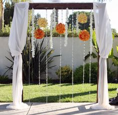 great idea... adorned with hanging rose pomanders, strings of white dendrobium orchids and crystal stands. We used sheer white flowy material to soften the frame.
