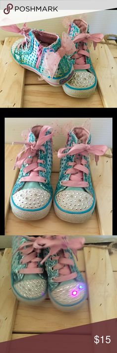 Skechers TwinkleToes Shuffles Pixie Bunch High-Top Lightly worn Skechers Twinkle Toes Shuffles Pixie Bunch Toddler Girls' Light-Up High-Top Sneakers. Toddler size 8. She'll light up the room in these Pastel Pink & Baby Blue high-tops adorned with glitter, bows, and metallic hearts! Please Note: stones are NOT missing from toe; these are twinkling lights that are triggered by movement.   SHOE DETAILS Hidden Zipper for easy entry/exit.                 Lace-up closure Padded footbed & Flexible…