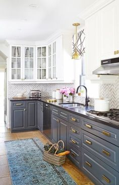 grey and white cabinets with a chevron tile backsplash and brass touches