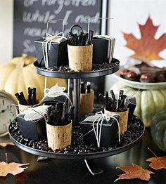 Throw a Grown-Up Halloween Party | Midwest Living- The plot sweetens    After dinner, move the storytelling away from the table with a tantalizing sideboard of dark and decadent sweets. We used a tiered server (stacked cake plates or plates on pumpkins would work as well) to offer black jelly beans, votive cups filled with licorice sticks and wrapped dark chocolates. Framed and scattered colorful dried leaves add an easy and cost-free decorative element.