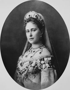 """Grã-duquesa Elizabeth Feodorovna em 1897. Ela está em pé virada para a esquerda com a cabeça voltada para a câmera. Ela está usando um vestido adornado com uma faixa e uma tiara e véu. Suas jóias inclui colares, medalhas e ordens do Império Russo. A fotografia é assinada """"Ella"""" e datado de 1897."""