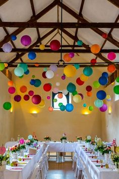 rainbow of bright paper lanterns hanging from rafters over tables