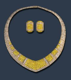 AN IMPRESSIVE SUITE OF DIAMOND JEWELRY, BY VAN CLEEF & ARPELS Comprising a necklace, of bombé V-shaped design, the articulated pavé-set diamond band enhanced at the front with graduated circular-cut yellow diamond panels; and a pair of ear clips en suite, mounted in 18k gold