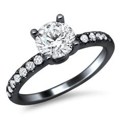 18k Black Gold Round Diamond Engagement Ring - Here's a simple but very elegant & sophisticated solitaire .93 carat Round Diamond Engagement Ring set in 18k Black Gold. It features an excellent cut .50 carat round diamond with SI1 in diamond clarity & G in color quality set atop of the ring. It's also surrounded by .43 carats of round diamonds in VS2-SI1 clarity & F in color stones down its sides. The ring's top measures 5.4mm wide. All of the diamonds are 100% natural…
