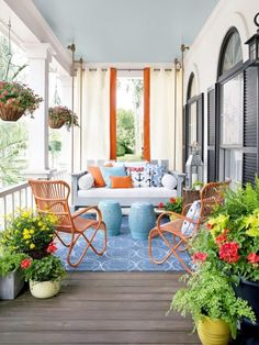 Patio decorating inspiration with orange pops of color on outdoor curtains and chairs, love the offset of blue on the rug and swinging couch decorative pillows
