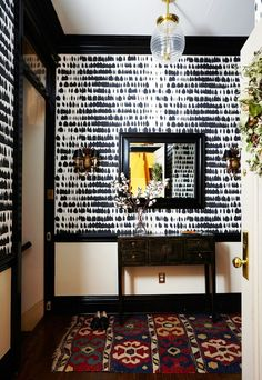 Chic hallway with printed wall paper, a vintage rug, and a vintage pendant light