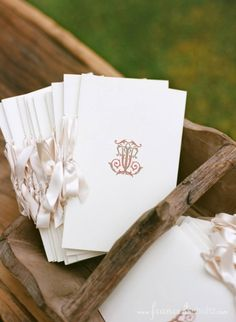 Wedding - ceremony programs in a rustic basket with Victorian monogram of bride and groom's first initials.
