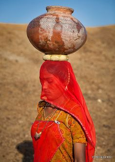 Asia | Woman carrying a bowl on her head, India