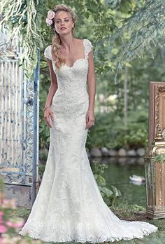 Brides: Maggie Sottero. See more details from Maggie Sottero  Lace fit-and-flare wedding dress, sprinkled with glittering Swarovski crystals. Finished with sweetheart neckline and covered buttons over zipper and inner elastic closure. Detachable beaded lace cap-sleeves sold separately.