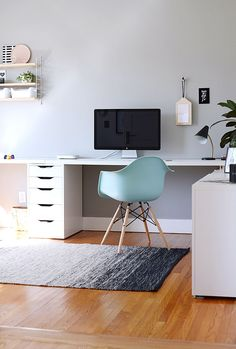 This contemporary home office hits all the right notes! A white wraparound desk w/ plant decor & a fun mint chair are the perfect accent to the amazing hardwood flooring.