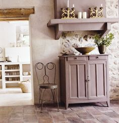 I love the rustic look of the stone wall with the tile floor.  The chair is adorable!