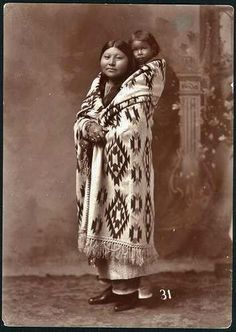 Commanche Indian portrait of a standing woman in blanket with her baby on her back 1895-1900 (ca)