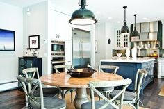 Echoing your kitchen lighting fixture with a similar (but not matching!) piece over your kitchen table ties the spaces together while still providing some necessary distinction between the two.