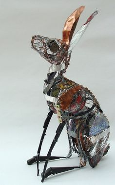 Highland Hare 2007/8  Recycled metal objects, steel wire, copper wire, old biscuit tins    66cm x 26cm x 38cm    This sculpture is made from a whole variety of found objects such as cutlery, keys, guitar wires, copper cylinder and tartan biscuit tin! The legs are from car windscreen wipers.    All the pieces are assembled and stitched onto a wire armature which is also very much a part of the final piece.