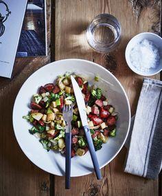 Gros plan de pommes de terre et de légumes coupés en dés, dans un saladier blanc posé sur une table en bois.