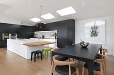 cuisine ouverte vers la salle à manger équipée de meubles noir matte avec crédence à design marbre gris et blanc