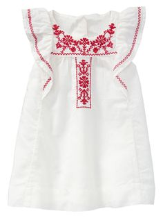 Flutter sleeves. Slight shirring at round neckline. Embroidered accents at front and sleeves. Rear button placket. Fully lined. Includes a diaper cover.