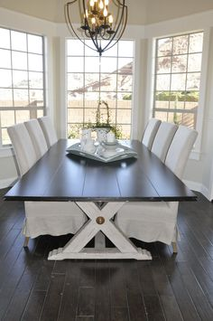 Farmhouse table, slipcovered chairs, wood floors, neutral decorating & especially love all the windows ♡