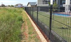 Black polyester coated high security clearvu fence for house protection, grass land and a swimming pool in yard.
