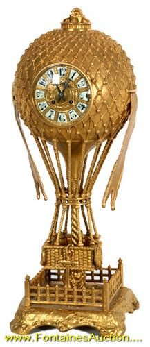 Large French Bronze Balloon Clock. The case depicts a hot air balloon with a woven basket below and is anchored to the ground within a fenced platform. Has a gold dore finish. Dial has applied Arabic numerals and fancy black hands; typical round French brass time and strike movement, signed Japy Freres. 27 in. high.