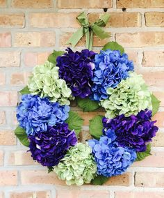 Welcome guests into your home with this stunning green, blue and purple hydrangea Spring door wreath! This wreath is made of 9 hydrangea faux flowers and leaves. These hearty and full flowers sit on a 14 inch circular metal frame. Wreath is finished off with a beautiful matching bow to hang wreath from!!!  This wreath can be customized by flower colors. Please message me what colors you would like and I will try to match it as best I can! I love to customize and individualize my wreaths…