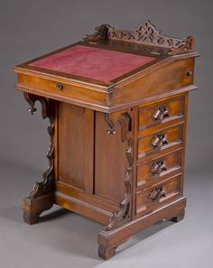 A walnut Davenport writing desk. c.1860s. Scrolling leaf pierced gallery on top and finials; slanted lid with red leather surface lifts to reveal small drawers; matching side doors with four carved grape leaf handles, left side are blind drawers; hidden compartment on right side for pen and inkwell.