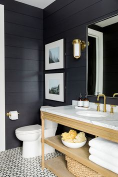 black panelled wall + blonde wood double sink cabinet + open shelving + brass hardware + b/w patterned floor tile