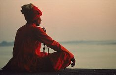 Man with rosary meditating on the banks of the River Ganges, Varanasi, India